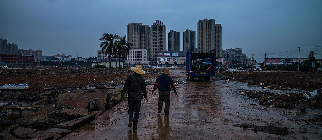 Workers walk on a path at a demolished industrial area in Dongguan, China. (© Lam Yik Fei, Getty Images)