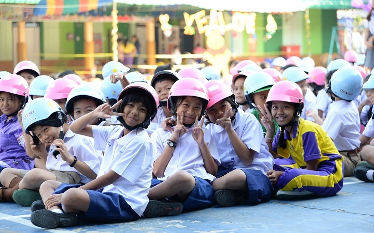 A poster displayed in Thai elementary schools to encourage students to wear bike helmets (left). Thai children don bike helmets donated by Denso (right) as part of the company's local traffic safety program. (Courtesy of Denso)