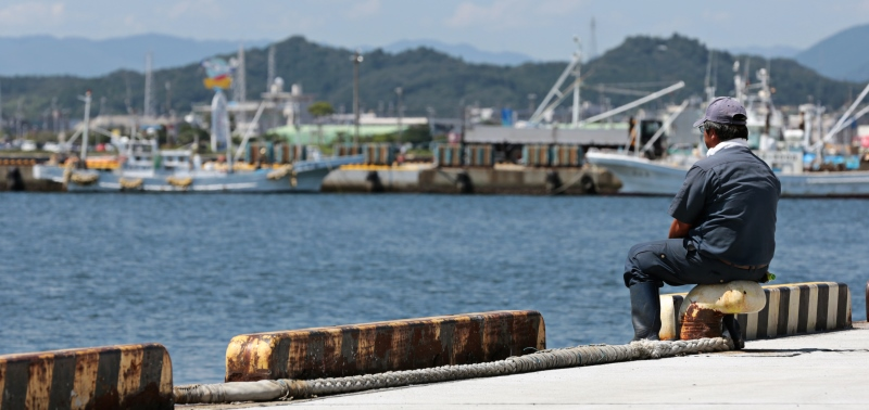 "A fisherman looks out to sea in Iwaki, Fukushima Prefecture, after the government announced in August 2013 that it will take ""emergency measures"" to tackle radioactive water spills at the Fukushima nuclear plant. ©Yuriko Nakao/Bloomberg via Getty Images"