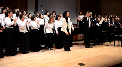 Mayuzumi, center, and composer Akira Senju, right, with the members of Japan Choral Harmony and the Men