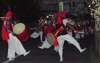 Groups of musicians and dancers make their way through the community at night during the Bon festival.