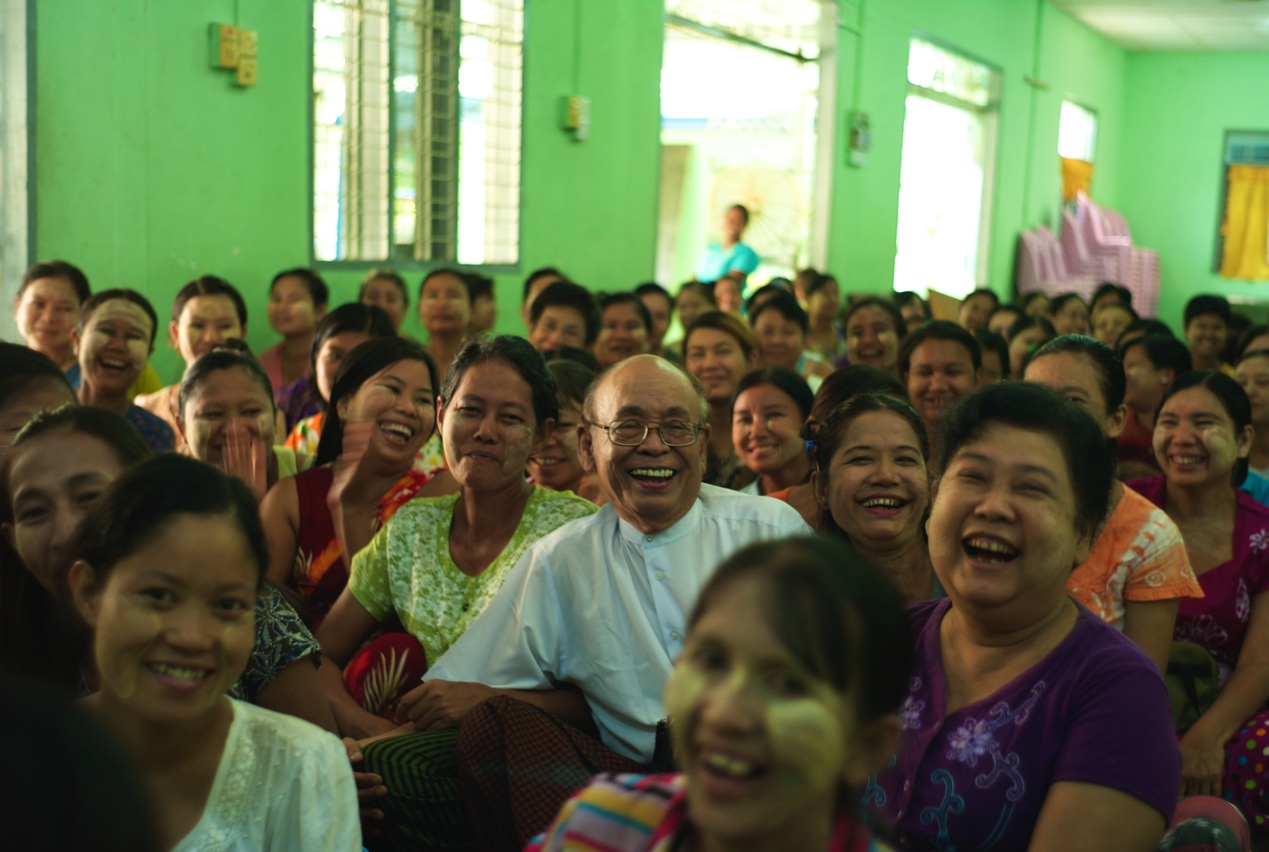 Customers gather at a community center in Myanmar. In the center is the president of Gojo's local subsidiary.
