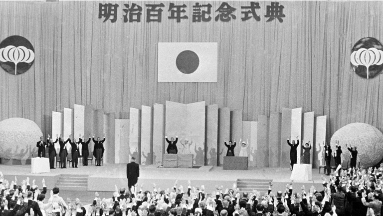 Prime Minister Eisaku Sato leads the hall in shouts of banzai at a grand ceremony commemorating the Meiji centennial, held on October 23, 1968, at the Budokan in Tokyo. At center stage are the former emperor and empress. ©Kyodo News