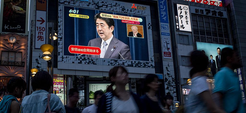 Pedestrians in Tokyo walk past a screen showing a live broadcast of Prime Minister Abe delivering his WWII anniversary statement on August 14, 2015. © Chris McGrath/Getty Images